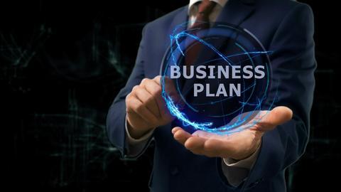Businessman shows concept hologram Business plan on his hand フォト