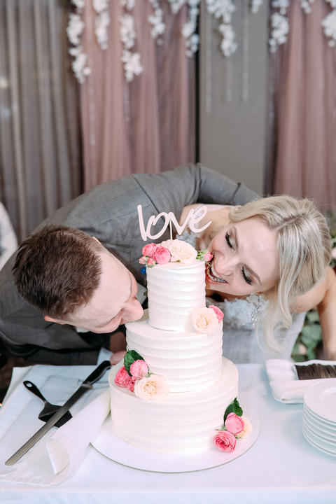 The bride and groom bite the wedding cake at the same time フォト
