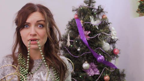 Girl tired to decorate Christmas tree, garland in the mouth Live Action