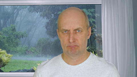 Face angry man looking in camera on background view from window on tropical rain Footage