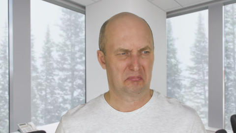 Face disgusted man with dislike on background window with view on snowfall in Live Action