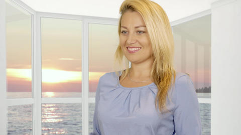 Woman receiving gift in red box on window background with evening sunset in sea Footage