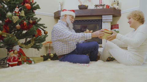 Old woman and man lie on the fluffy carpet and exchange Christmas presents Footage
