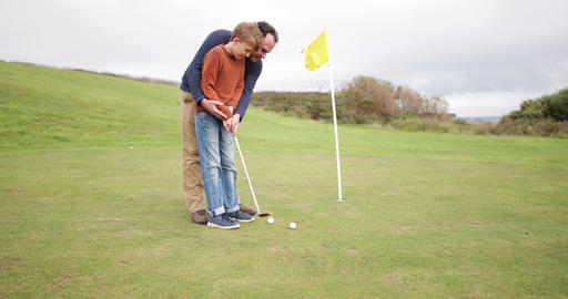 Father teaching son how to play golf ビデオ