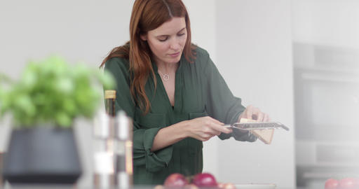 Adult female grating parmesan over a dish Footage