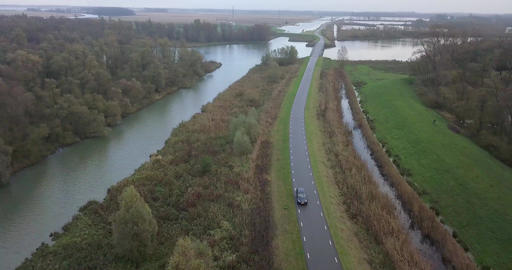 4k Cinematic shot of a car driving on a road near the canals in Holland Footage