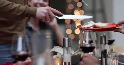 Close-up adult male serving Christmas meal to friends Footage