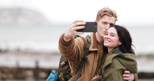 Young couple taking a selfie on a camping trip Live Action