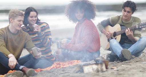 Group of young adult sitting around campfire socialising Footage