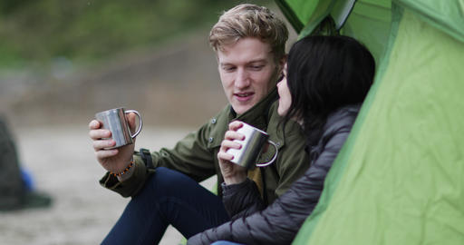 Young couple camping on the beach in fall Footage