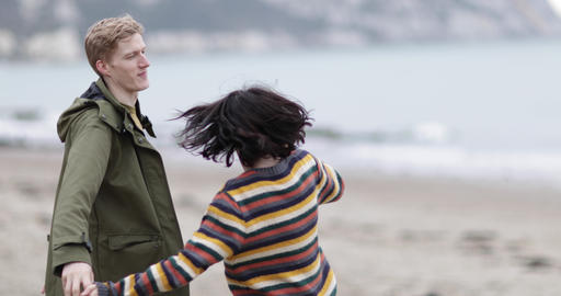 Young couple dancing on a beach in winter GIF