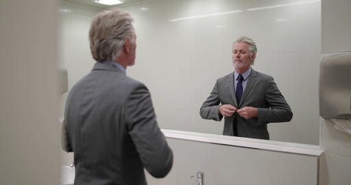Businessman looking in a mirror preparing for business meeting Footage