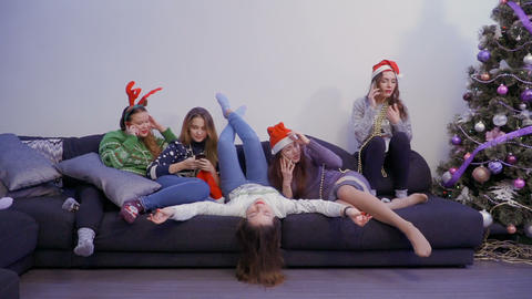 Five girls use their phones relaxing at sofa ビデオ