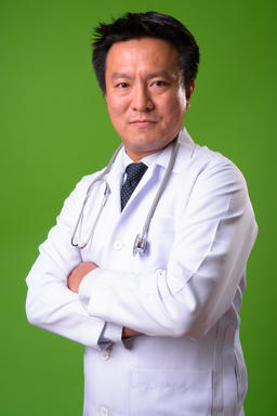 Mature Japanese man doctor against green background Photo