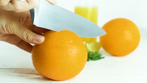 Closeup slow motion footage of woman cutting orange in two halves with big knife Footage