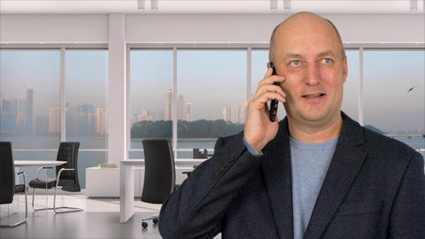 Businessman talking to mobile phone in office on background window Footage