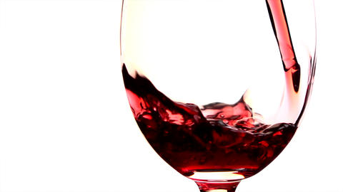 Red wine poured into glass on white background ビデオ