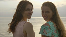 Two young Caucasian girls in dresses walking along shallow water at sunset, turn Footage