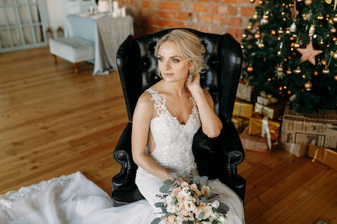 The bride in the Studio sitting on a black leather chair フォト