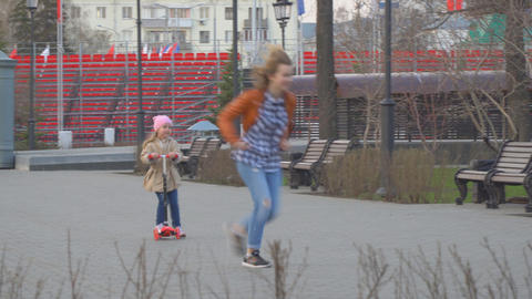 Little Girl riding in the Park on a scooter Footage