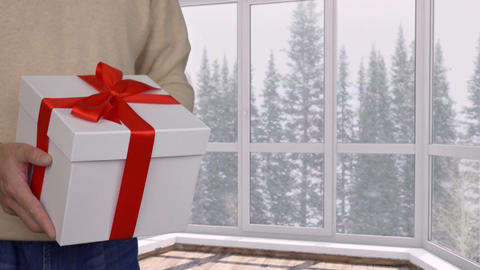 Man presenting gift box with red ribbon on christmas or new year, snowfall GIF