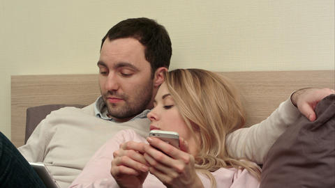 Young couple lying in bed, man using digital tablet, bored woman using Live Action