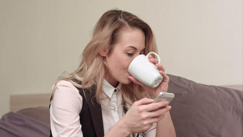 Woman using cellphone in bed at night and drinking tea Footage