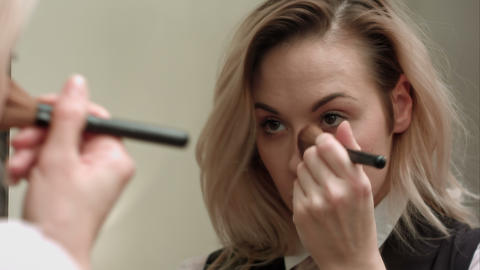 Woman in front of mirror putting make up on Footage