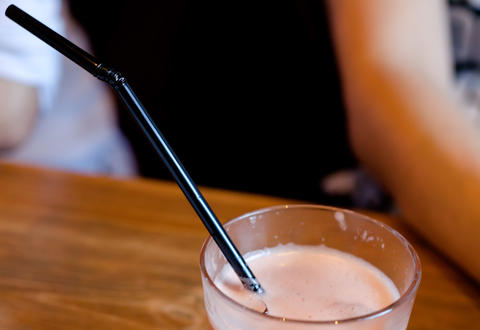 Fresh grapefruit juice and black long straw in the glass .Copyspace top フォト