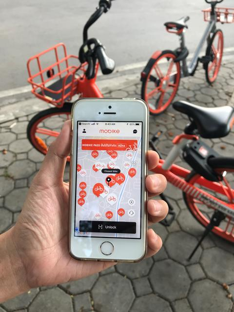 """user is using application on iPhone for """"mobike"""" rental bicycle フォト"""