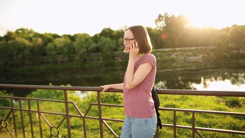 Pretty fashionable woman talking on the phone on a city bridge on the sunset Footage