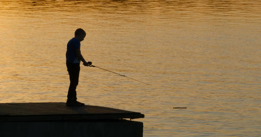 Silhouette of a young fisherman with fishing rod Footage