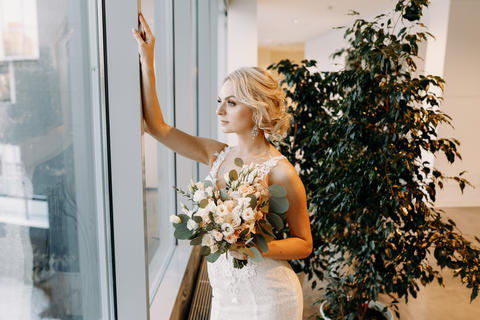 Beautiful bride in a white dress stands near the window at the hotel フォト