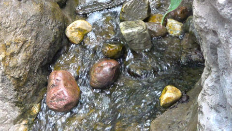 Water flowing around rocks in stream. Slow motion Footage