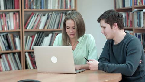 Two students studying together using laptop Footage