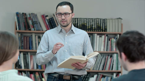 Young male teacher holding book talking in classroom Footage