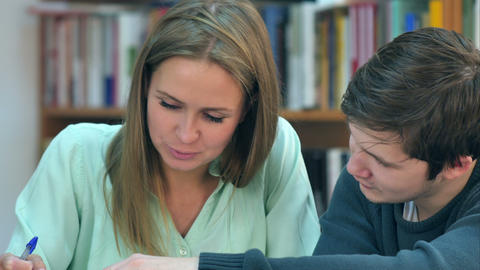 Two young students reading a book in library Footage