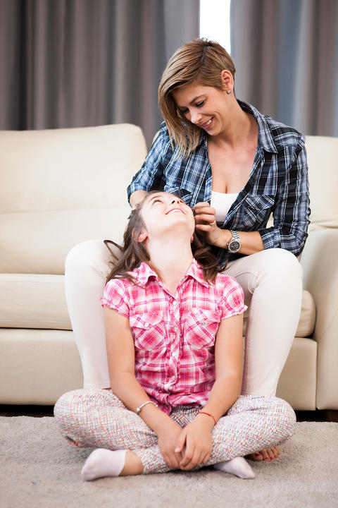 Mother combs her daughter hair フォト