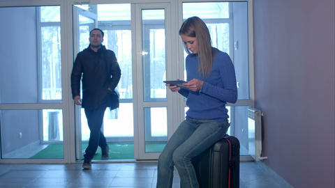 Young man entering the doors and talking to smiling woman with tablet sitting on Live Action