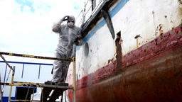Workers tear off paint on metal in repairs process at shipyard Footage