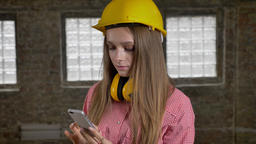 Young beautiful focused girl builder watching her smartphone, network conception Footage