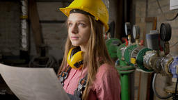 Young serious girl builder is watching plan of building, watching above Footage