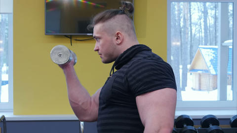 Muscular man working out in gym doing arm exercises Footage