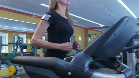 Active young woman running on treadmill in sport club Footage