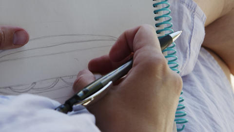 Girl artist in sunglasses draws sketches in notebook Live Action