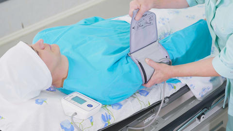 man lies and nurse fixes device to measure blood pressure Footage