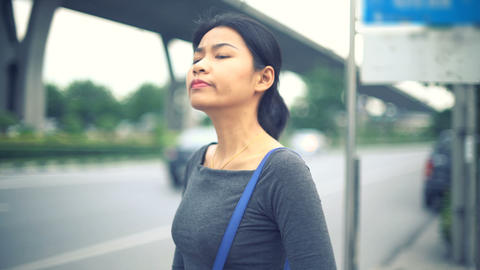 Young Asian Woman waiting at bus stop toned video Footage