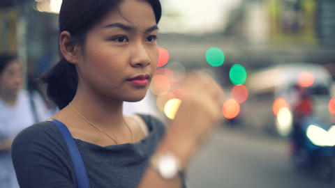 Portrait of young Asian Woman waiting at bus stop toned video Footage