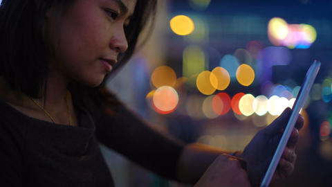 Pretty Asian Woman using tablet in night city Footage