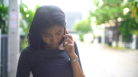 Young asian girl talks on phone in townhouse village Footage